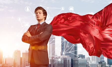 Young confident businessman wearing red cape against modern city background Reklamní fotografie