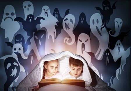 Enthusiastic little girl and boy reading book in bed after bedtime. Kids in pajamas with flashlight hiding under blanket together. Fearful children and imaginary monsters on deep blue background. Stock Photo
