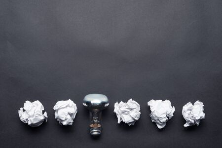 Lightbulb and crumpled white paper balls on black background. Successful solution of problem. Think outside the box. Business motivation with copy space. Genius idea among failing ideas metaphor. Stock Photo