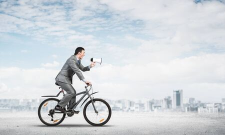 Businessman with megaphone on bike at sunny day. Marketing and advertising campaign. Manager in business suit riding bicycle on road. Male cyclist on background of blue sky and city on horizon Stok Fotoğraf - 124842593