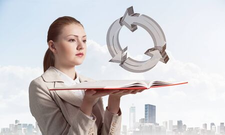 Woman looks at transparent recycle 3d symbol above opened notebook. Renewable energy source concept. Elegant girl with book on background of cityscape and cloudy blue sky.