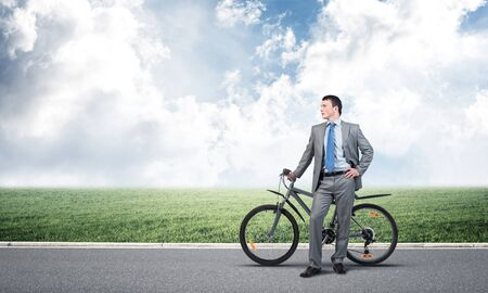 Young man wearing business suit and tie standing on asphalt road with bike. Businessman with bicycle on background of blue cloudy sky. Outdoors male cyclist holding bicycle, having break in riding.