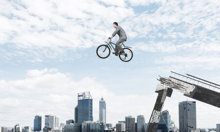 Businessman on bike jumping from broken bridge. Man wearing business suit riding bicycle in air. Cyclist on background of cityscape and blue sky. Eco-friendly transport and outdoor activity.
