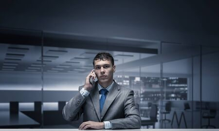 Young man talking on phone and looking at camera. Businessman sitting at desk in office interior. Portrait of guy wears business suit and tie. Business person using smartphone for conversation