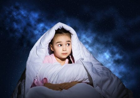 Scared girl with pillow hiding under blanket. Startled kid lying in his bed at home. Little girl afraid of dark. Covered child not sleep at night. Girl in pajamas on background of deep blue sky. Stockfoto