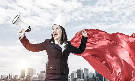 Young confident businesswoman wearing red cape against modern city background screaming in megaphone Stockfoto