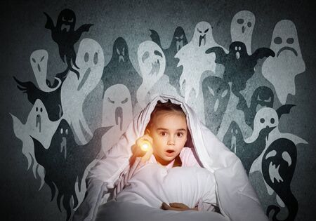 Surprised girl with flashlight hiding under blanket. Amazed kid sitting in his bed at home. Fear of the dark. Little child in pajamas afraid of ghosts at night. Nightmare fantasy and imagination.