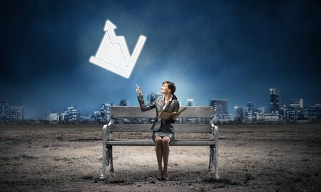 Young woman with open book on wooden bench outdoor. Beautiful girl in business suit finger pointing at growing diagram symbol. Modern cityscape panorama at night. Business analytics and statistics Stockfoto