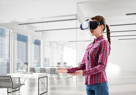Young woman wearing virtual reality helmet in modern office interior. Mixed media