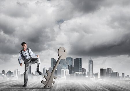 Determined businessman against modern cityscape breaking with leg stone key figure Stockfoto
