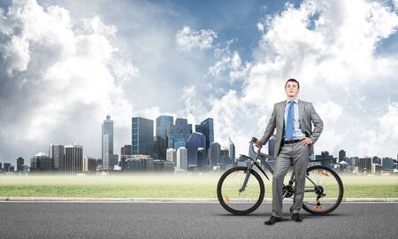 Young man wearing business suit and tie standing on asphalt road with bike. Businessman with bicycle on background of business center. Outdoors male cyclist holding bicycle, having break in riding. Stockfoto