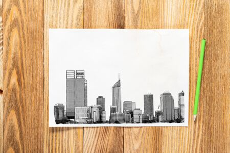Modern city center pencil draw. Panorama of urban modern city with high skyscrapers sketch on wooden surface. Sheet of paper on textured natural wooden background. Architecture agency concept