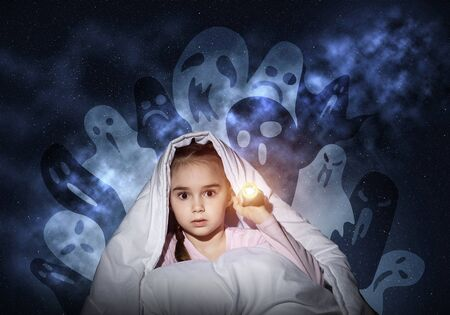 Scared girl with flashlight hiding under blanket from imaginary ghosts. Kid sitting in bed on night sky background. Covered child in pajamas not sleep at night. Mysterious phantoms in darkness. Stockfoto