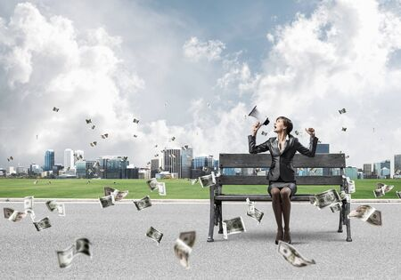 Young woman with megaphone sitting on wooden bench. Money income concept. Female motivational speaker under falling money banknotes. Businesslady shouting in loudspeaker. Money investment and banking. Stockfoto