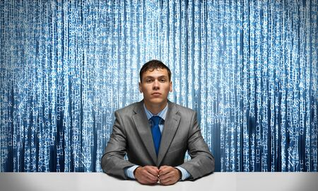 Handsome serious man with folded hands on binary computer code background. Online safety consultant in business suit and tie sitting at desk. Internet security and confidentiality assistance. Stockfoto
