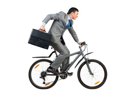 Businessman on bike hurry to work. Young man scared to be late. Corporate employee in grey business suit with suitcase riding bicycle. Male cyclist isolated on white background. Rush hour concept