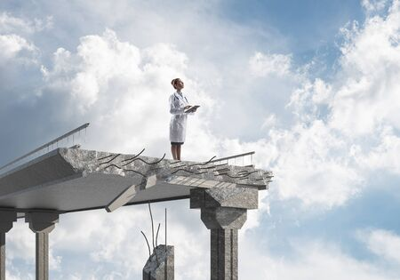 Confident medical industry employee in white medical suit holding tablet in hands while standing on broken bridge with landscape view on background. Medical industry concept Stockfoto