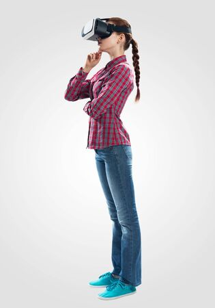 Young woman in checkered shirt and jeans wearing virtual helmet. Woman standing with folded hands. Cyber technology and new virtual reality. Studio photo by side view girl against gray background