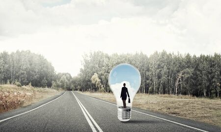 Young businesswoman trapped inside of light bulb on asphalt road Stockfoto