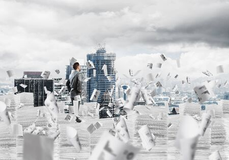 Confident businessman in suit standing on pile of documents among flying papers with cityscape on background. Mixed media. Stockfoto