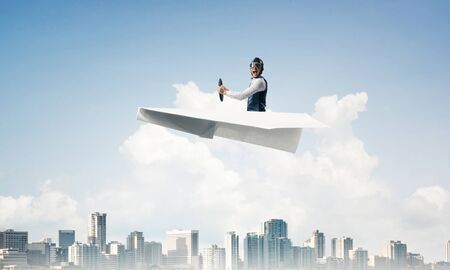 Scared pilot with open mouth sitting in paper plane and holding steering wheel. Aviator driving paper plane above business center in blue sky. Cityscape with high skyscrapers and office buildings. Imagens - 124922773