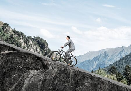 Businessman riding uphill by bike. Nature landscape with copy space. Man in business suit riding bicycle on mountain road. Cyclist on background of blue sky. Healthy lifestyle and outdoor activity
