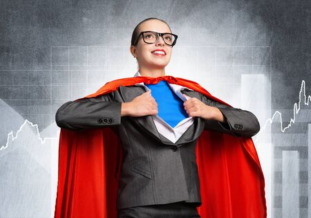 Happy business woman tearing off her shirt and transforming in super heroine. Smiling business lady with red hero cape on financial graph background. Brave super woman ready for new achievements.
