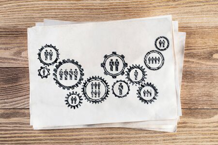Corporate social responsibility concept with group of rotating gears and cogs. Human resources cooperation sketch on wooden surface. Workplace with paper stack lying on wooden desk.