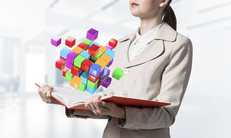 Woman showing colorful geometric 3d cubes composition above open book. Digital technology and innovation solutions concept. Businesswoman with open book on blurred light background.
