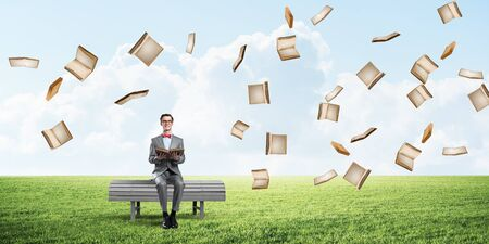 Funny man in red glasses and suit sitting on bench and reading book Zdjęcie Seryjne - 125248980