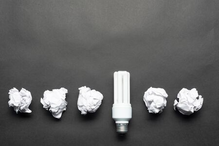 Fluorescent lamp and crumpled white paper balls on black background. Idea generation and brainstorming motivation. Business concept of successful and failing ideas. Creative and genius solutions 스톡 콘텐츠