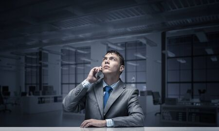 Young man talking on phone and looking upward. Businessman sitting at desk in conference room. Portrait of guy wears business suit and tie. Business person using smartphone for conversation