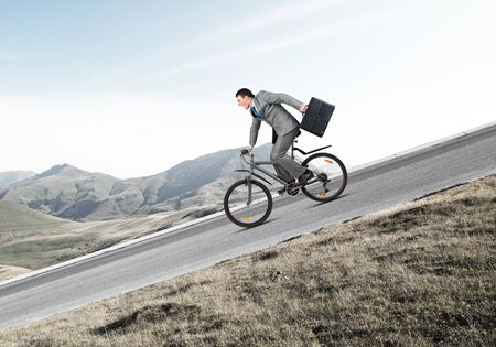 Young man on bicycle fast riding downhill at sunny day. Businessman on bike hurry to work. Corporate employee wearing business suit with suitcase on cycle outdoor. Male cyclist on mountain road 版權商用圖片