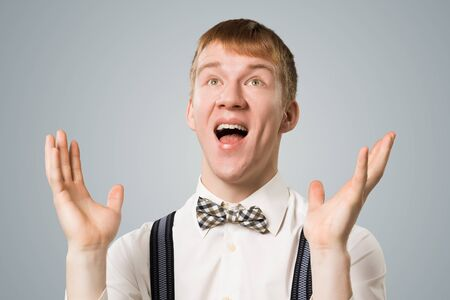 Friendly hipster smiling broadly with satisfied and pleasant look. Emotional redhead boy raising hands in hooray gesture. Portrait of guy wears white shirt, bow tie and suspenders on grey background Фото со стока