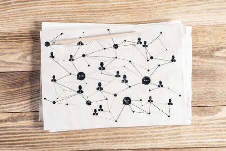 Matita di struttura di social network disegnata a mano con icone umane e intersezioni. Schizzo di comunicazione aziendale su superficie di legno. Vista dall'alto del posto di lavoro con carta bianca e matita sdraiata sulla scrivania in legno