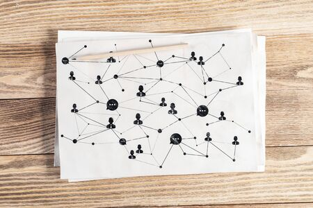 Social network structure pencil hand drawn with human icons and intersections. Business communication sketch on wooden surface. Top view of workplace with white paper and pencil lying on wooden desk Banque d'images