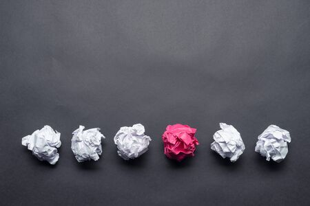 Crumpled pink paper ball among white balls on black background. Dissimilar solution of problem. Think outside the box. Business motivation with copy space. Unique idea among failing ideas metaphor. Stock Photo
