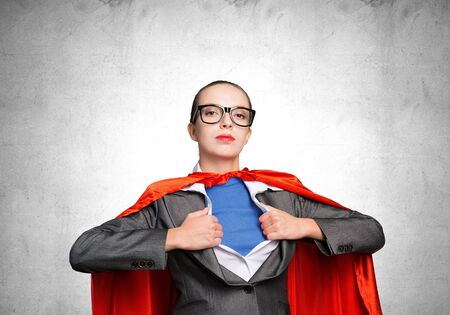 Attractive young business lady in red hero cape on grey wall background. Portrait of business woman super heroine. Career development and leadership. Confident super woman ready for new challenges.