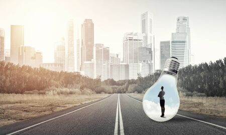 Young businesswoman trapped inside of light bulb on asphalt road 스톡 콘텐츠