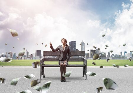Business woman taking selfie photo or chatting with smartphone. Attractive girl using mobile phone on wooden bench. Mobile marketing and communication. Cityline panorama with falling money banknotes Stock Photo
