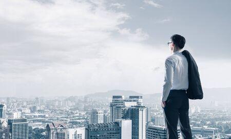 Jeune homme d'affaires élégant avec une veste sur l'épaule à l'écart Banque d'images