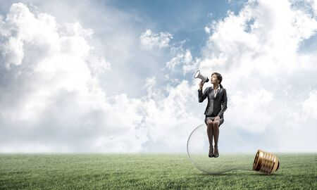 Young woman with megaphone sitting on big light bulb. Female speaker advertising new service or product on green meadow. Businesslady shouting in loudspeaker. Business marketing and announcement.