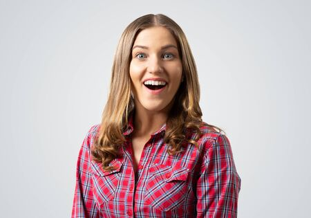 Happy charming girl smiling wide. Emotional young woman has surprised facial expression. Portrait of delighting girl wears red checkered shirt on grey background. People emotion and expression. Stock Photo