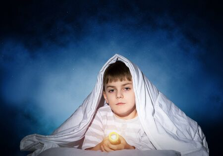 Serious child with flashlight hiding under blanket. Attentive kid lying in his bed at home. Fear to sleep in darkness at night. Portrait of little boy in pajamas on background of deep starry sky. Stock Photo - 126009204