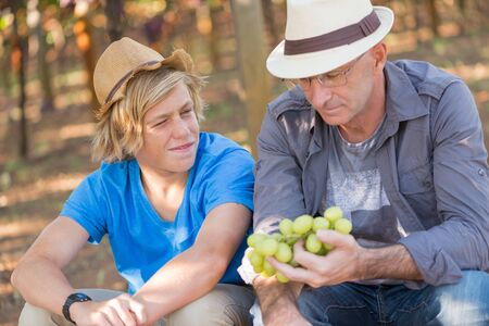 Winegrowers in straw hats relaxing in garden at sunny day. Father and son gardeners speaking and looking each other. Senior and young winemakers in their vineyard. Small family winery business Stock fotó