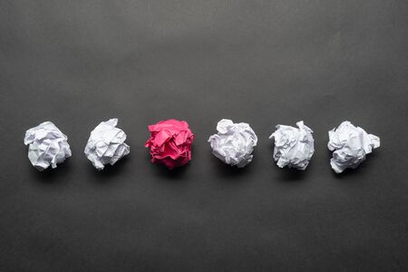 Crumpled pink paper ball among white balls on black background. Extraordinary solution of problem. Business motivation with copy space. Unique and different experience. Idea generation and imagination Stock Photo