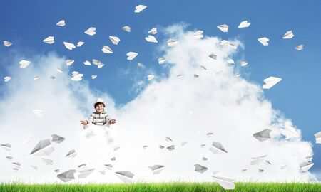 Young little boy keeping eyes closed and looking concentrated while meditating on cloud among flying paper planes with bright and beautiful landscape on background. Stock Photo