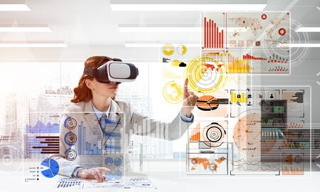 Business woman in suit using virtual reality goggles while sitting inside bright office building. Concept of modern technologies for business needs. 스톡 콘텐츠