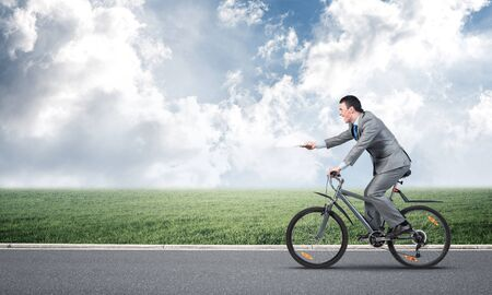 Businessman with paper documents in hand on bike. Deadline for submitting paperwork. Corporate employee in grey business suit riding bicycle on highway. Cyclist on background of blue cloudy sky.