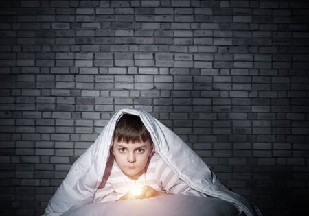 Serious child with flashlight hiding under blanket. Attentive kid lying in his bed at home. Fear to sleep in darkness at night. Portrait of little boy in pajamas on background of brick wall.